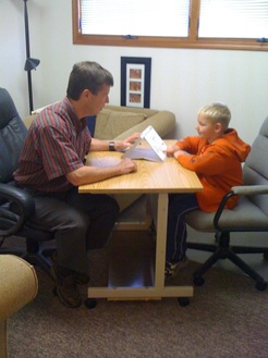 Photo of Dan Nolan PhD administering a test to a child